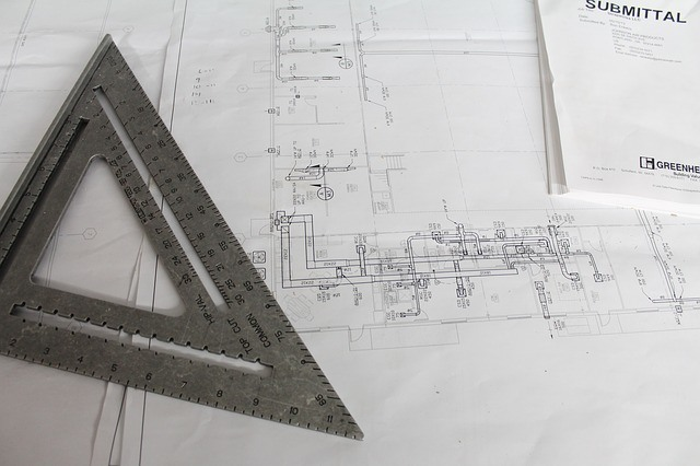 An architect scale laying on top of a construction blueprint. Contractors must submit blueprints in order to get building permits