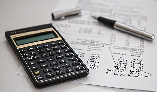 A calculator and pen laying on top of a construction budget. Building permits vary in price depending on various factors