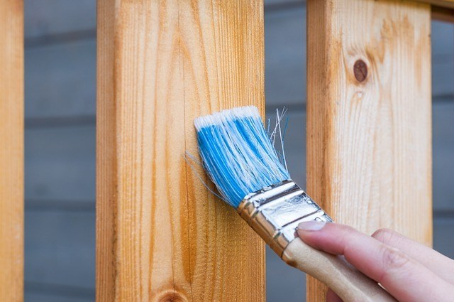 A handyman painting a wooden fence. Building permits are not required for certain construction duties