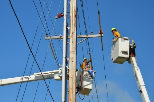 Two electricians up in the air fixing a telephone pole. Many construction companies require their employees to maintain OSHA safety certifications