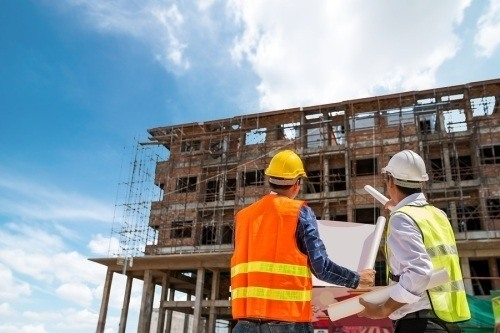 Two contractors on a job site looking up at a building, holding construction plans. a construction foreman is typically an experienced tradesman who oversees workers on a job site
