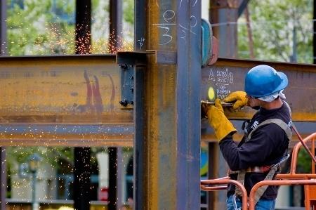 Construction worker working on a steel beam. OSHA primarily focuses on hazardous jobs
